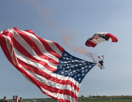 Dana Bowman skydives with a huge American flag to celebrate Camp Perry's First Shot Ceremony on Monday. Bowman lost his legs in a 1994 skydiving accident with the U.S. Army's Golden Knights but continues to skydive with prosthetic limbs.