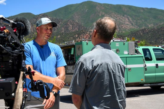 Prineville Hotshot Alex Robertson speaks with members of the press at the Storm King Fire news conference on Saturday, July 6, 2019, near Glenwood Springs, Colo., marking 25 years since the lives of 14 wildland firefighters were lost on Storm King Mountain, which looms in the background.