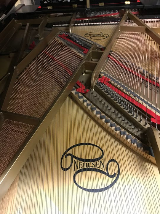 The inner workings of the double grand piano built by Peter Nehlsen of Washington Island, with his name on the single soundboard. It's one of just two double pianos known to be working in the world.