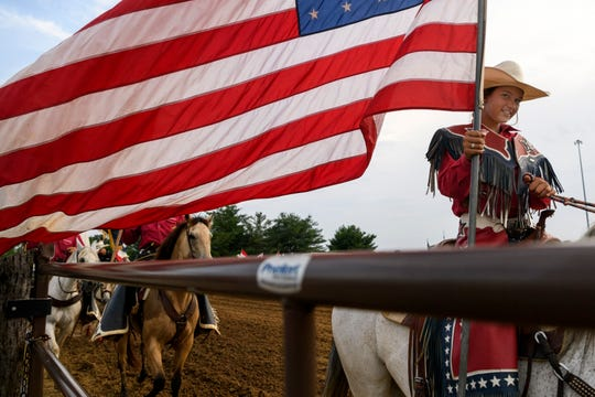 Oralee Madison, 11, waves an American Flag around the show arena at the beginning of the Lone Star Rodeo show at the Henderson County Fairgrounds in Henderson, Ky., Saturday, July 6, 2019. Two nights of the professional rodeo kicked off the 2019 Henderson County Fair season, which will be happening every weekend through the month of July.