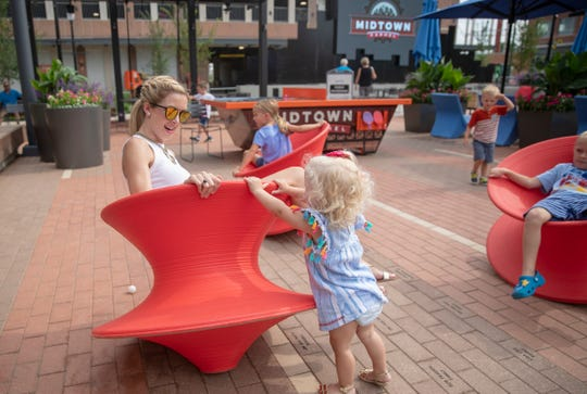 Juli Ring, Carmel, plays with her daughter Lydia Ring, 1, at Midtown Plaza, Carmel, Friday, July 5, 2019.