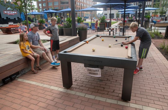 Players enjoy a game of pool at Carmel's Midtown Plaza.