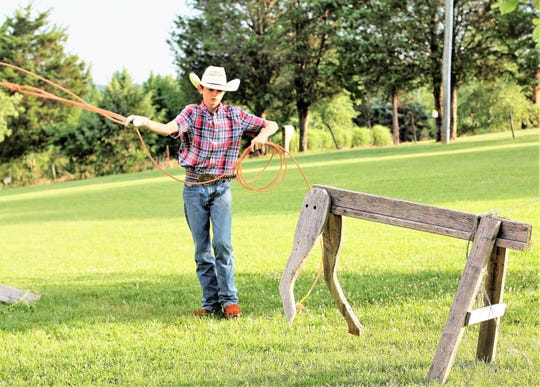 """Jake McMurray spends hours practicing his roping skills, using plastic """"dummy"""" cow heads and a handmade sawhorse shaped cow."""