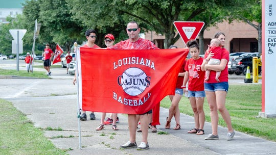 Mourners gather down the route for the funeral procession Monday to pay their respects to UL baseball coach Tony Robichaux.