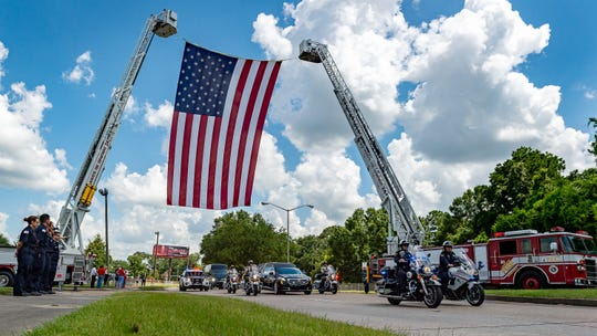 The funeral procession for UL baseball coach Tony Robichaux makes its way down Cajundome Boulevard on Monday.