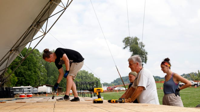 Alex Urbanski, left, hammers a sheet of particle board into place on the Wendel Concert Stage before the 2019 Lancaster Festival at Ohio University Lancaster. The COVID-19 pandemic forced the cancellation of this year's festival, but the festival board is working on three options for the 2021 event.