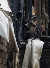A praying statue sits surrounded by melted siding and charred wood on the deck to the upstairs apartment at 208 Perry Street in Lancaster.