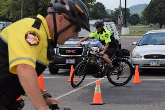 Fairfield County Sheriff's Office Deputy Mark Bennington practices tight turns as Deputy T. J. Strawn prepares for his turn. The sheriff's office has brought the bike team back after nearly 20 years.