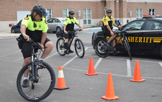 Fairfield County Sheriff's Office Lt. Marc Churchill maneuvers through cones as deputies T.J. Strawn and Mark Bennington watch. The sheriff's office brought the bike team back after nearly 20 years.