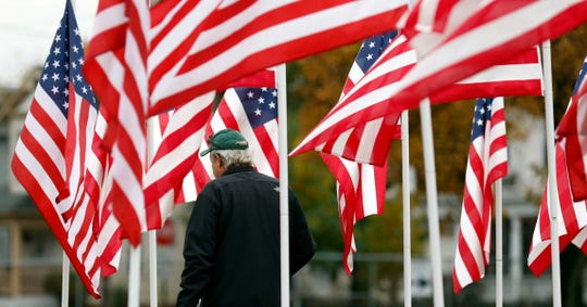 Scott Parker, from Lancaster, walks through the field of flags last year at the Fairfield County Fairgrounds in Lancaster. Parker and his wife, Michele Parker, were visiting the annual Freedom's Never Free event at the fairgrounds. This year's event will run from Oct. 30 to Nov. 2