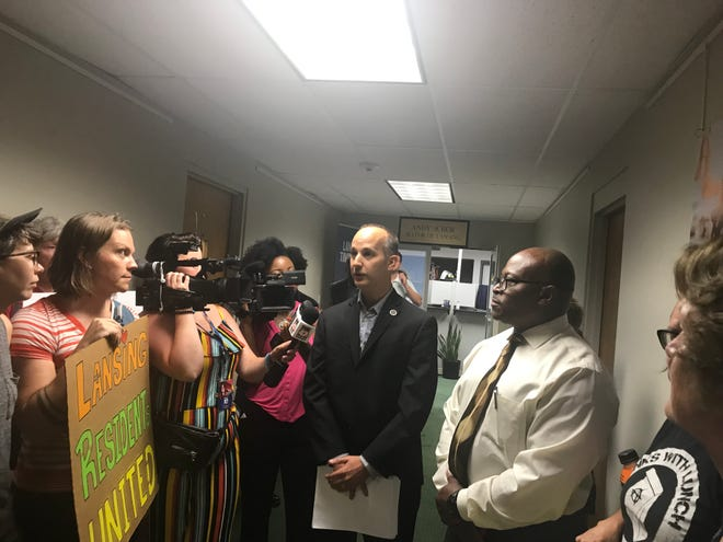 Protestors hand deliver letters calling for police reform to Lansing Mayor Andy Schor on the ninth floor of City Hall on Monday, July 8, 2019.