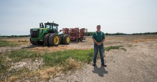 Duane Smuts, of Smuts Farms in Charlotte, poses for a portrait at the family farm Monday afternoon, July 8, 2019. Due to wet fields, he has not been able to plant the field behind him since last fall's corn cutting season. The field will not be planted this year, he said.