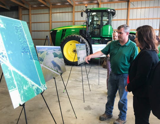 Duane Smuts, of Smuts Farms in Charlotte, shows Gov. Gretchen Whitmer an aerial photo showing standing water in one of his fields on Monday afternoon, July 8, 2019. The photo of the field was taken on July 1, he said.