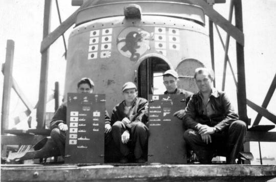 Four crew members holding scoreboards on USS Guavina (SS 362). Note the battle insignia and scoreboard of enemy vessels destroyed painted on forward Conning Tower. Pictured left to right: Max Clayton Baxter, Darris Ellis Province, LaVergne C. Ward, and Dennis Leroy Erickson.