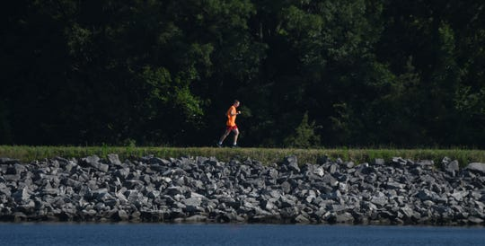 A runner enjoys a mild summer morning as he orbits Shelby Reservoir Number 3 on Monday.