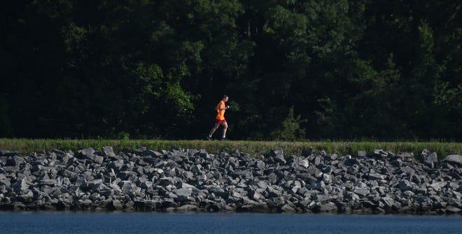 A runner enjoys a mild summer morning as he orbits Shelby Reservoir Number 3 on Monday.