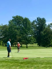 Elgin's Kayedon Martin putts while River Valley's Tyler Booker looks on during the Heart of Ohio Junior Golf tournament at Marion Country Club on Monday.
