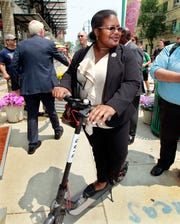 (D) State Representative LaKeshia Myers checks out an electric scooter after Gov. Tony Evers signed bill for SB 152 for the Electric Scooter Bill at the Milwaukee Public Market on Monday, July 8, 2019.