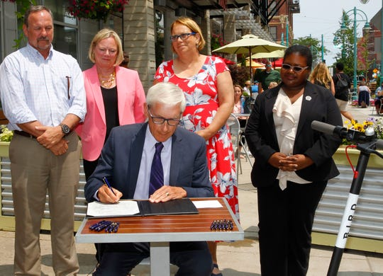 Gov. Tony Evers signs bill for SB 152 for the Electric Scooter Bill at the Milwaukee Public Market on Monday, July 8, 2019. Watching from left are (R) State Representative Mike Kuglitsch, (R) State Representatie Cindi Duchow, (D) State Representative Christine Sinicki and (D) LaKeshia Myers.