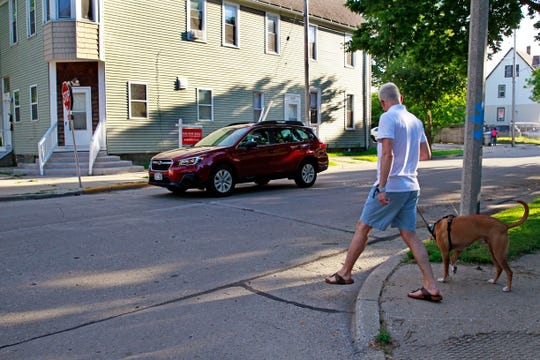 Justin Smith, who lives in the 2700 block of North Booth Street, walks his dog, Graham, at the corner of North Booth and  East Hadley streets one afternoon last week.  Smith and other residents have seen an increase in drivers speeding and running stop signs in the neighborhood.