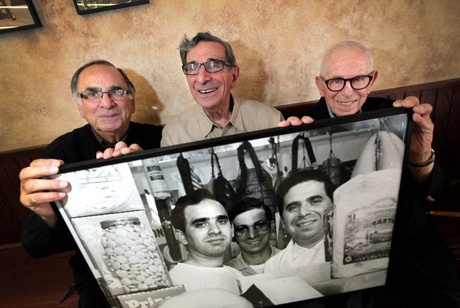 Glorioso brothers Ted, left, Eddie, center, and Joseph hold a photo of themselves, circa 1930.