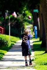 A  boy plays with a football on Booth Street, where residents say drivers often ignore stop signs and drive too fast.