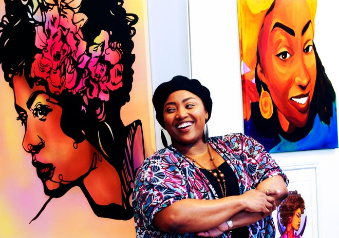 Artist Jasmine Wyatt poses next to some of her artwork at the Bronzeville Collective, 393 West North Ave.