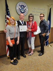Paul Szecsi (second from left) is joined by his family after taking the oath to become a U.S. citizen on Friday in Fort Smith. Shown above are (from left) daughter Stacia Shirley, wife Kim Szecsi and son Connor Szecsi.