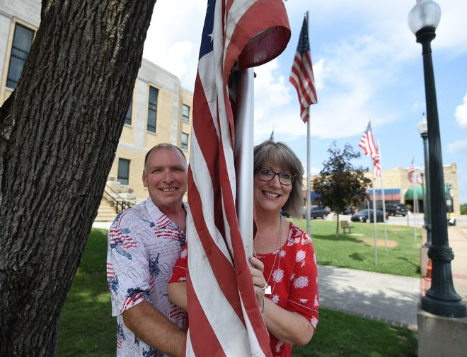 Paul Szecsi (left) and his wife, Kim, pose on either side of an American flag on the courtyard on the Baxter County Courthouse. Paul Szecsi is originally from Canada and recently became a naturalized U.S. citizen after years of applying.