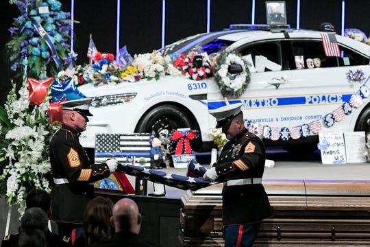 U.S. Marines fold the flag from the casket of Officer John Anderson.