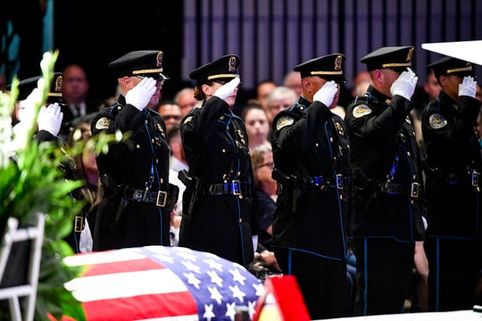 Metro Nashville Police officers salute during the memorial service for Officer John Anderson.