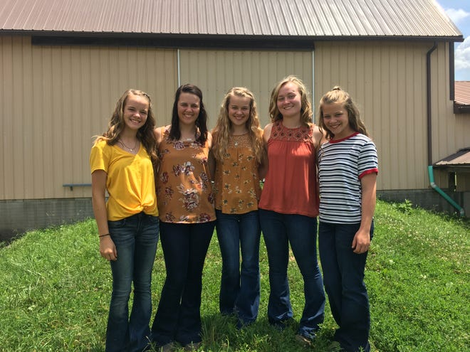 the Graham sisters (from L to R),  Alicia, Michaela, Shala, Chelsea, and Marissa pose for a photo outside one of their barns.