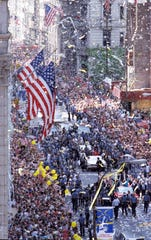 Ticker tape falls from skyscrapers as vehicles carrying Secretary of Defense Dick Cheney, Joint Chiefs Chairman Colin Powell, and Desert Storm Commander Gen. H. Norman Schwarzkopf make their way along Broadway at the start of the Operation Welcome Home parade in New York, on June 10, 1991.  (AP Photo/Susan Ragan)