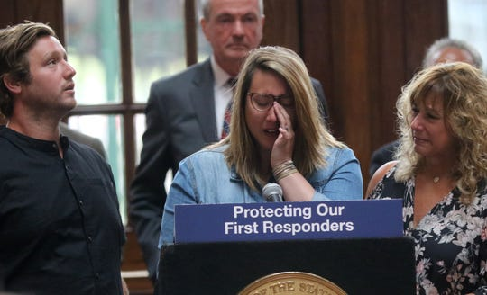 Allison Canzanella, of Chicago, gets emotionally as she spoke about her father, Thomas Canzanella, who was  President of the Professional Firefighters Association of NJ and Deputy Chief at the Hackensack Fire Department. Gov Murphy (background) later signed the  Thomas P. Canzanella Twenty First Century First Responders Protection Act, in her father's name. Allison's brother, Thomas Canzanella and mother, Diane Canzanella, are shown beside her.  Monday, July 8, 2019
