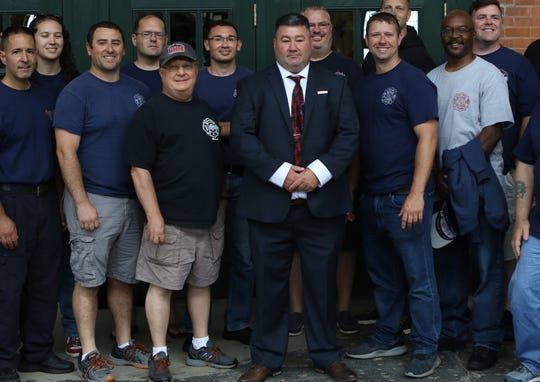 Bill Ricci (center), poses with members  of the Clifton Fire Department after Gov. Murphy (not shown), signed The Bill Ricci World Trade Center Rescue, Recovery, and Cleanup Operations Act in Jersey City. Monday, July 8, 2019