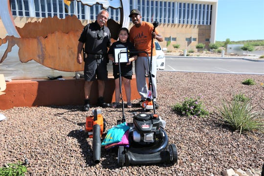 Natoria Martinez, 10, stands with Las Cruces Codes Enforcement Officer Rudy Adame, left, and Rodney Smith Jr., right, founder of Raising Men Lawn Care service. Natoria recently completed RMLC's challenge to mow 50 lawns and was awarded Monday, July 8, 2019.