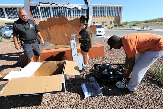 Natoria Martinez, 10, opens gifts she received from Rodney Smith Jr., founder of Raising Men Lawn Care service, as Las Cruces Codes Enforcement Officer Rudy Adame stands watch, Monday, July 8, 2019, in Las Cruces.