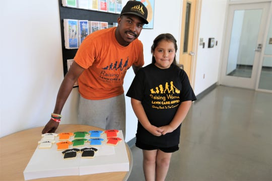 Natoria Martinez, 10, presented Rodney Smith Jr., founder of Raising Men Lawn Care, a nonprofit in Huntsville, Alabama, with some baked cookies as a gift, Monday, July 8, 2019, in Las Cruces.