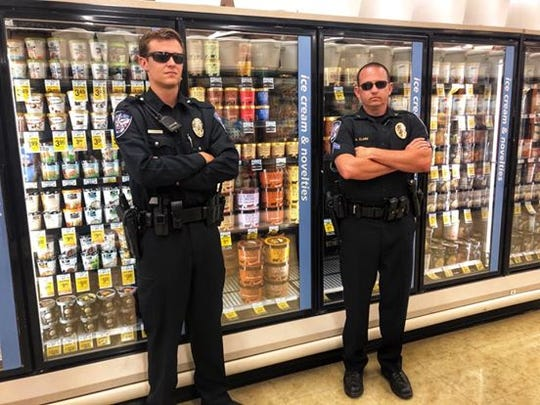 "Two officers stand in front of the ice cream section in a Texas store. ""There will be no Blue Bell licked in this Texas supermarket,"" after video went viral on social media striking the ""Ice Cream Licking Challenge."""