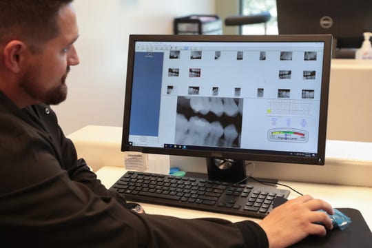 Dr. Chris Atchison looks at a patient's x-rays at the Sage Initiative, Indio, Calif., May 30, 2019.