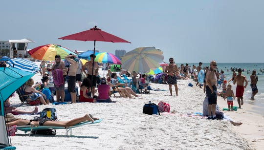 Beachgoers enjoy a warm sunny day Monday at Pensacola Beach. Forecasters say a tropical depression could develop in the Gulf of Mexico later this week.