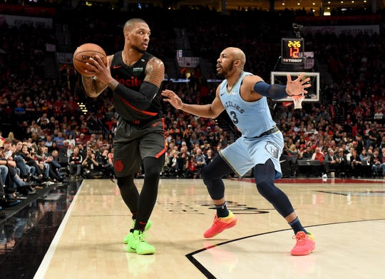 Apr 3, 2019; Portland, OR, USA; Portland Trail Blazers guard Damian Lillard (0) looks to pass the ball on Memphis Grizzlies guard Jevon Carter (3) during the second half of the game at the Moda Center. The Blazers won 116-89. Mandatory Credit: Steve Dykes-USA TODAY Sports