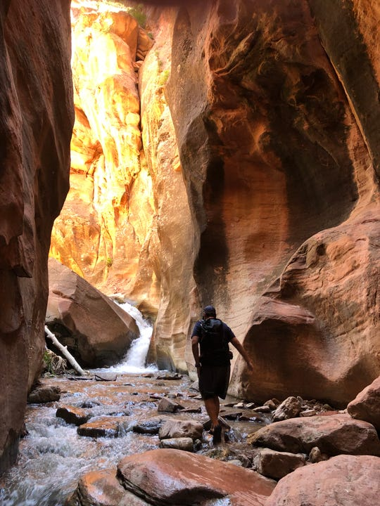 Francisco Aguilar of Las Vegas hikes through the slot canyon to the second of three falls.
