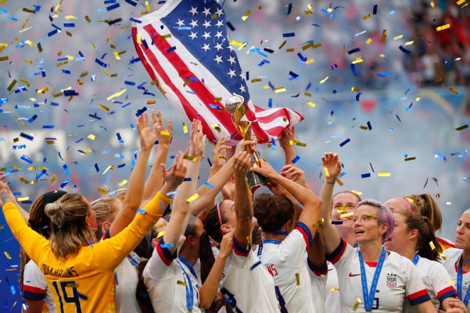 United States players celebrate with the World Cup trophy after defeating the Netherlands in the championship match of the FIFA Women's World Cup France.