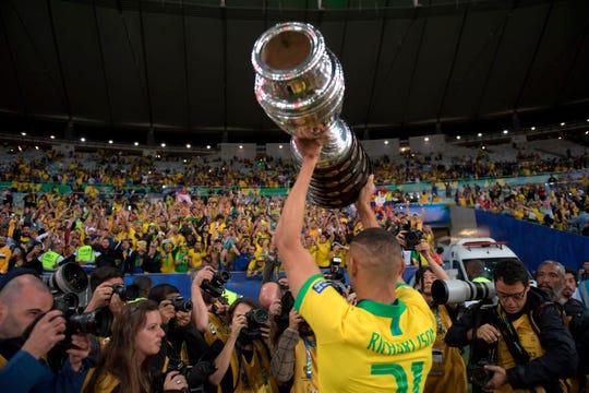 Richarlison, jugador de la 'verde amarela', muestra la copa a la fanaticada de Brasil.