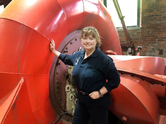 Natural Power Group co-owner Sarah Bower-Terbush stands in front of a power turbine at the company's hydroelectric site in Wappingers Falls. She and her husband sell renewable power to local customers from three hydroelectric sites they operate in the Hudson Valley. Customers say they like investing their money locally in clean power.