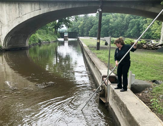 Natural Power Group co-owner Sarah Bower-Terbush cleans debris from the canal that feeds the company's hydroelectric site in Wappingers Falls. She and her husband sell renewable power to local customers from three hydroelectric sites they operate in the Hudson Valley. Customers say they like investing their money locally in clean power.