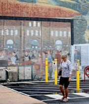 "Cindy Edmonds of Dover walks past the ""From Farm to Market"" mural by artist Marion Kendall Stephenson on Beaver Street after meeting with friends in downtown York Monday, July 8, 2019. York County History Center recently launched an interactive virtual tour on its website featuring 35 historical York City murals. Bill Kalina photo"