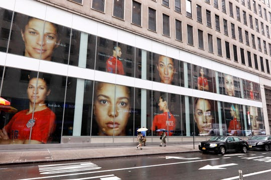 Portraits of the USA women's soccer team members are visible in the windows of a building on Fifth Avenue, in New York, Thursday, June 13, 2019. Women's soccer engages the U.S. every four years, then disappears for most fans like Brigadoon. In the wake of the Americans' record-setting fourth World Cup title Sunday, July 7, 2019, the hard part remains ahead: the weekly work of boosting the National Women's Soccer League.