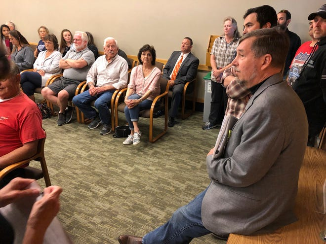 Sen. Brian Boquist, right, waits prior to a hearing at the state capital in Salem, Ore. July 8, 2019. A special committee of the Oregon state Senate is holding a hearing over the lawmaker's comments he made during a Republican revolt over climate legislation.